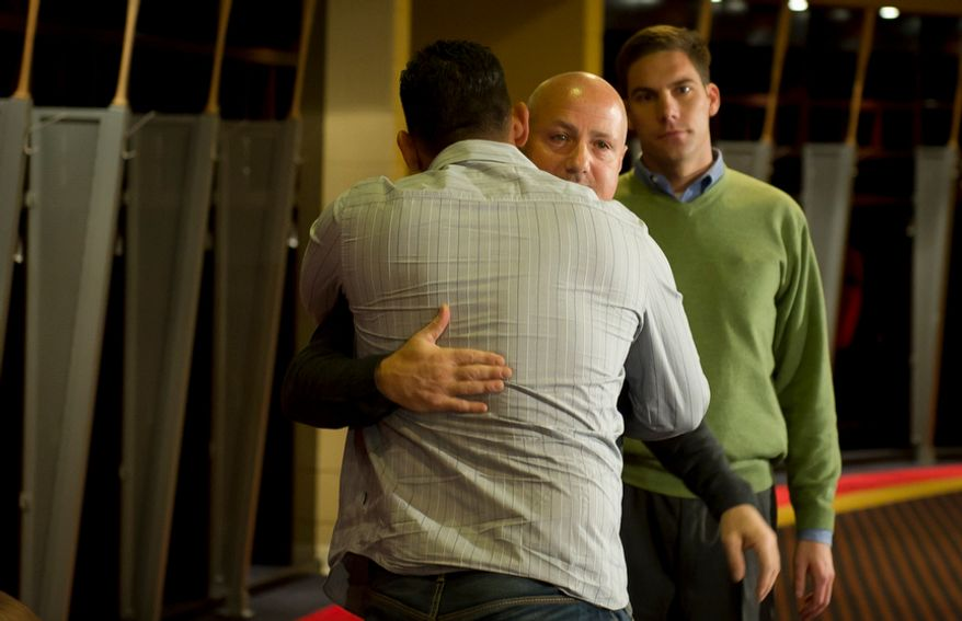 Washington Nationals' catcher (3) Wilson Ramos (left) gets a hug from Washington Nationals General Manager Mike Rizzo (right) following remarks to reporters about his recent abduction in front of his family home in Venezuela, in the team's clubhouse in Washington, DC, Friday, November 18, 2011. (Rod Lamkey Jr. / The Washington Times)