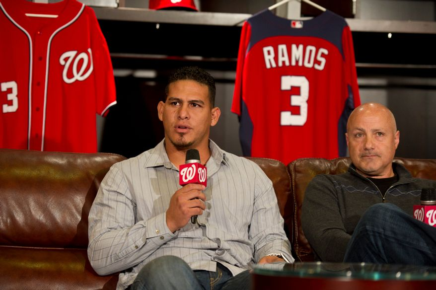 Washington Nationals' catcher (3) Wilson Ramos (left) is joined by Washington Nationals General Manager Mike Rizzo (right) during remarks to reporters about his recent abduction in front of his family home in Venezuela, in the team's clubhouse in Washington, DC, Friday, November 18, 2011. (Rod Lamkey Jr. / The Washington Times)