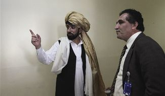 An Afghan delegate, Mahmood Khan Sulaiman Khial, left, gestures as he speaks with a colleague Gul Badshah Majidi on the third day of loya jirga or grand council in Kabul, Afghanistan, Friday, Nov. 18, 2011. Afghan President Hamid Karzai spoke Wednesday on the opening day of the meeting where the elders are discussing negotiations under way for a U.S.-Afghan agreement to govern the presence of U.S. troops after 2014, when most international forces are to have left or moved into support roles. (AP Photo/Musadeq Sadeq)