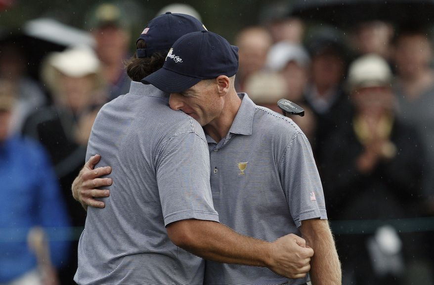 U.S. team's Phil Mickelson, left, is congratulated by his teammate Jim Furyk after sinking a winning putt on the 17th green during the Presidents Cup golf tournament at Royal Melbourne Golf Course in Melbourne, Australia, Saturday, Nov. 19, 2011. (AP Photo/David Callow)