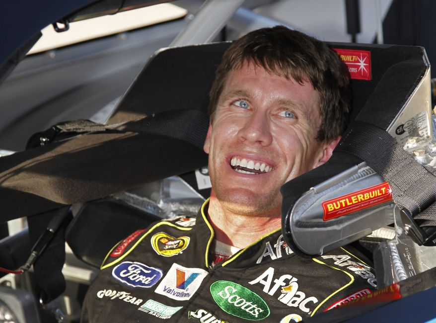 Driver Carl Edwards smiles after qualifying for Sunday's NASCAR Ford 400 Sprint Cup series auto race at Homestead-Miami Speedway in Homestead, Fla., Saturday, Nov. 19, 2011. Edwards won the pole position for the race. (AP Photo/Terry Renna)