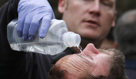 University of California, Davis, student Mike Fetterman, receives a treatment for pepper spray by UC Davis firefighter Nate Potter, after campus police dismantled an Occupy Wall Street encampment on the campus quad in Davis, Calif., Friday, Nov. 18, 2011. (AP Photo/Rich Pedroncelli)