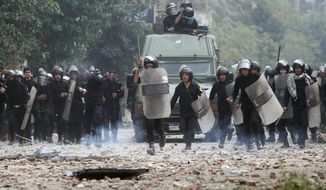 Egyptian riot police advance during clashes Sunday with protesters in Cairo's Tahrir Square. They battled for a second day with thousands of demonstrators demanding that a date be set for the handover of power from the military to a civilian government. (Associated Press)