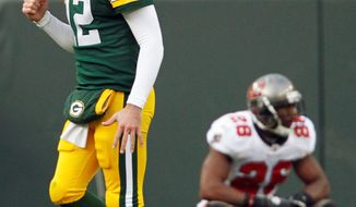 Green Bay quarterback Aaron Rodgers reacts to a touchdown run by John Kuhn in front of Tampa Bay's Kregg Lumpkin. The Packers beat the Buccaneers 35-26 to run their record to 10-0. (Associated Press)