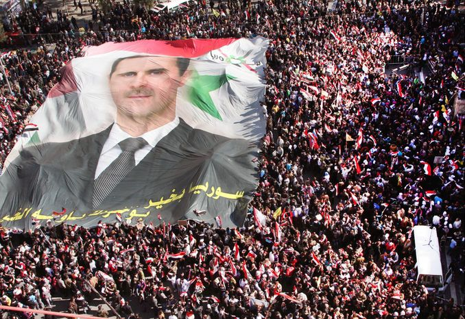 Pro-regime Syrians carry a huge portrait of President Bashar Assad during a demonstration to show their solidarity with him in Damascus on Sunday. (Associated Press)