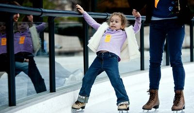 Lilla Harrigan, 5, holds tight to her mother Cheyenne Bsaies, of Fairfax, Va., as they skate during the opening weekend of the National Gallery of Art sculpture garden ice rink in Washington, D.C. on Nov. 20, 2011. (T.J. Kirkpatrick/ The Washington Times)