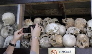 "A tourist takes pictures of human skulls of Cambodian Khmer Rouge victims at Choeung Ek stupa, better known as ""Killing field"" on the outskirts of Phnom Penh, Cambodia, Sunday, Nov. 20, 2011. (AP Photo/Heng Sinith)"