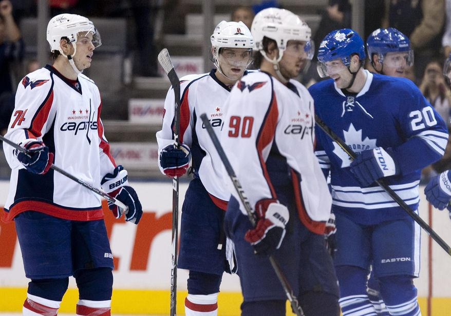 Washington Capitals' John Carlson, Alex Ovechkin and Marcus Johansson react as Toronto Maple Leafs' David Steckel celebrates scoring his team's seventh goal during third period in Toronto on Saturday Nov. 19, 2011. The Caps lost 7-1. (AP Photo/The Canadian Press, Chris Young)