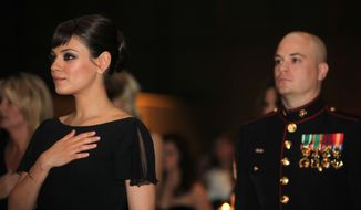 Sgt. Scott Moore and his guest, actress Mila Kunis stand during the National Anthem at the 236th Marine Corps birthday ball for 3rd Battalion, 2nd Marine Regiment, 2nd Marine Division in Greenville, N.C., on Friday Nov. 18, 2011. (AP Photo/Cpl. Johnny Merkley)