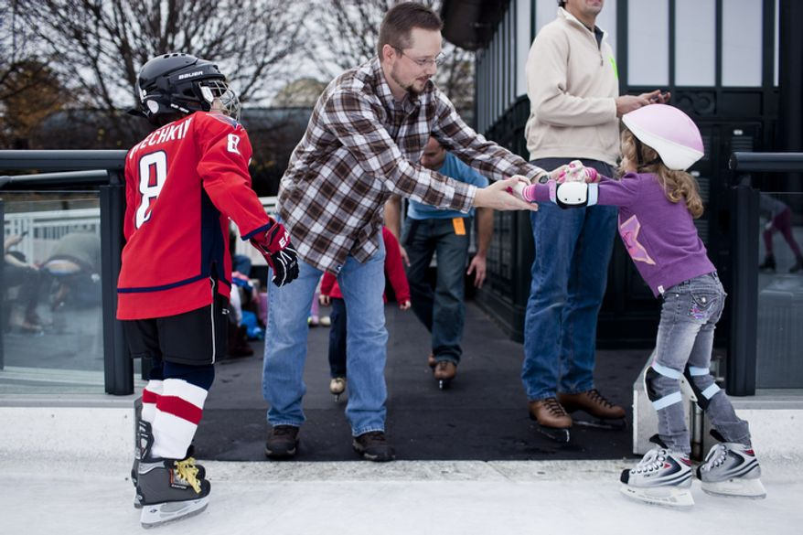 James Jordana, at center, of Sterling, Va., helps his daughter, Melanie, 5, across a gap in the railing as his son, Lukas, 7, dressed as the Capitols' Alex Ovechkin, watches during the opening weekend of the National Gallery of Art sculpture garden ice rink in Washington, D.C. on Nov. 20, 2011.(T.J. Kirkpatrick/ The Washington Times)