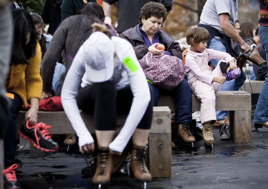 Naomi Leibowitz, 6, right, with her mother Wendy, of Bethesda, Md., puts on her skates. (T.J. Kirkpatrick/ The Washington Times)