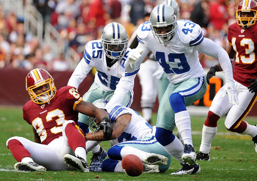 Washington Redskins tight end Fred Davis (83) fumbles during first quarter action, while Dallas Cowboys free safety Gerald Sensabaugh (43) looks to recover the ball at FedEx Field in Landover, Md., on Sunday, November 20, 2011. (Andrew Harnik/The Washington Times)