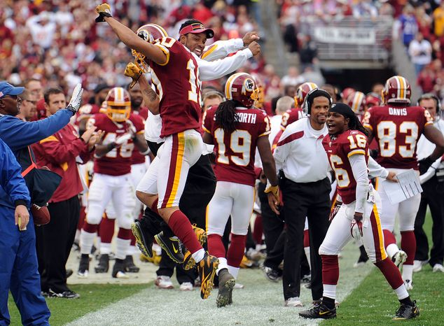 Washington Redskins wide receiver Jabar Gaffney (10) celebrates with sidelined wide receiver Santana Moss after scoring a go-ahead touchdown during second quarter action. (Andrew Harnik/The Washington Times)