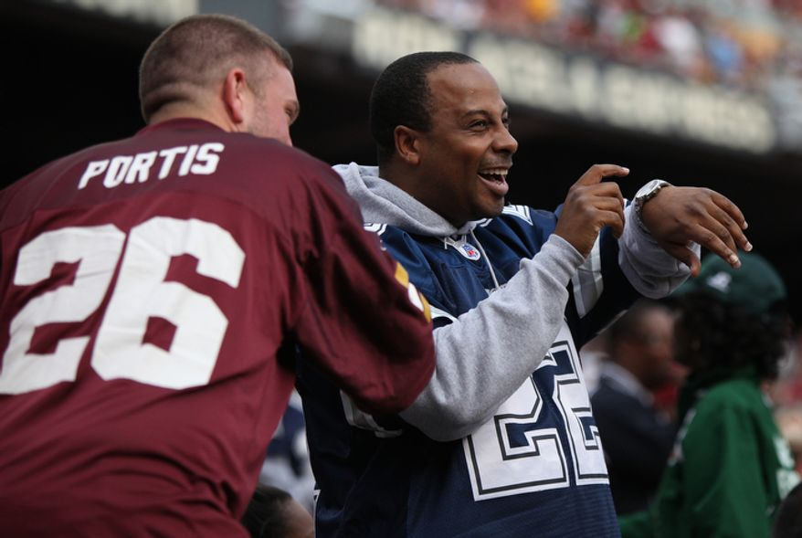 Keith Lewis, from Springfield, VA, left, playfully pushes Cowboys fan Aaron Holbert, of Silver Spring, MD as he points to his watch to let his friend know there is more time left in the game.  (Pratik Shah/The Washington Times)