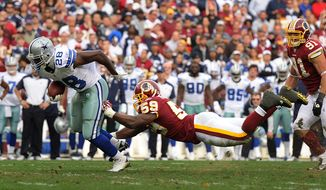 Washington Redskins inside linebacker London Fletcher (59) leaps to hold Dallas Cowboys running back Felix Jones (28) to a 4-yard gain on this third quarter reception. (Andrew Harnik/The Washington Times)
