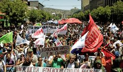 """People march through the streets of Valparaiso, Chile, last week demanding education reform. The sign at bottom translates to """"Put an end to profits! Free education now!"""" (Associated Press)"""