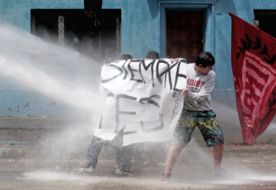 The force of a water cannon pushes back students in Santiago seeking education reform. Chile's schools were free to all students until the regime of Augusto Pinochet, which cleared the way for more private universities and a voucher system that directs billions in public funds to privately run high schools.