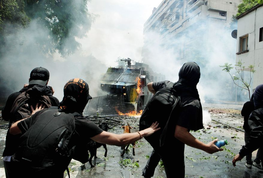 Protesters confront police in a vehicle spraying water during a protest Friday in Santiago demanding education reform.