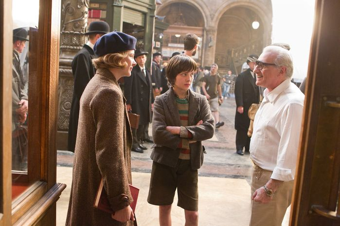 """Director Martin Scorsese talks to cast members Emily Mortimer (left) and Asa Butterfield on the set of """"Hugo,"""" Mr. Scorsese's first 3-D movie. The film is about a 12-year-old orphan who lives in a 1930 Paris train station. """"There's great potential for it,"""" he said of 3-D moviemaking. (Paramount Pictures via Associated Press)"""