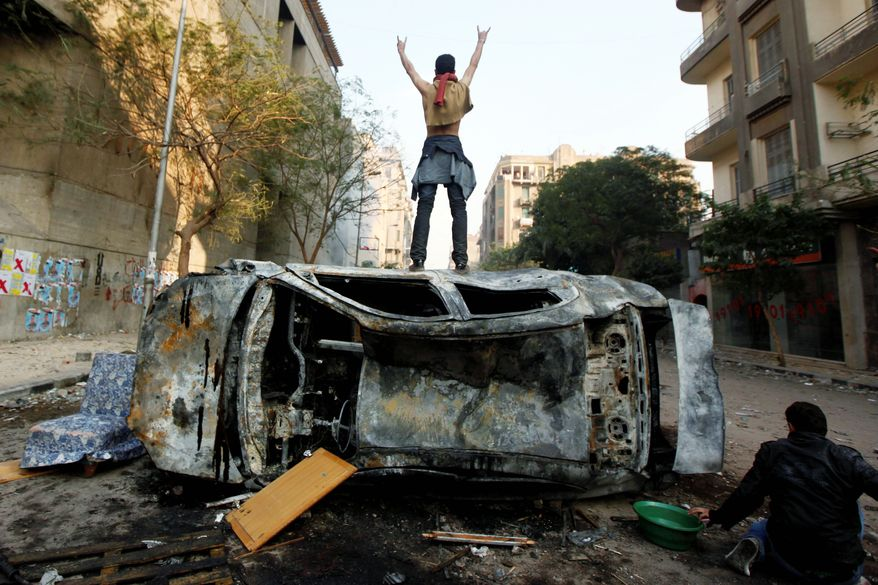 A protester stands on top of a burned car during clashes with Egyptian riot police, unseen, in Tahrir Square in Cairo on Monday. Security forces fired tear gas and clashed with several thousand protesters in the third straight day of violence that has killed at least two dozen people and has become the most sustained challenge yet to the rule of Egypt's military. (Associated Press)