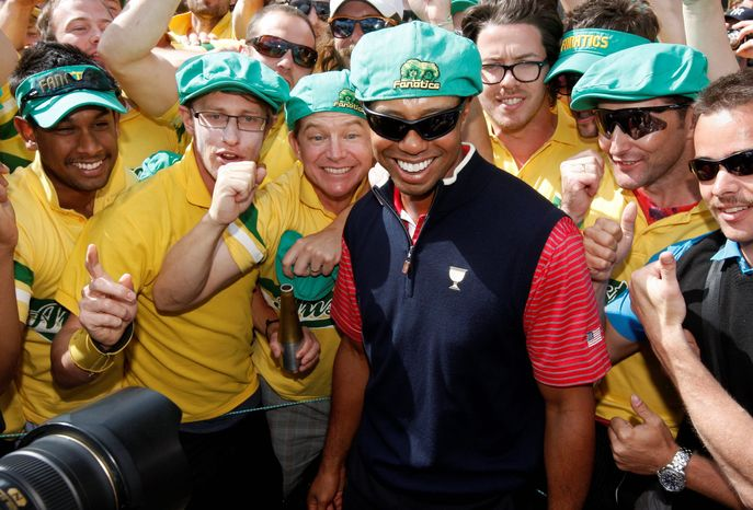 Tiger Woods poses with the Fanatics cheer squad at the 17th green after the Presidents Cup golf tournament at Royal Melbourne Golf Course in Melbourne, Australia, on Sunday. Woods' solid play at Presidents and the Australian Open is an encouraging sign to his fans that his form of old may be returning. (Associated Press)