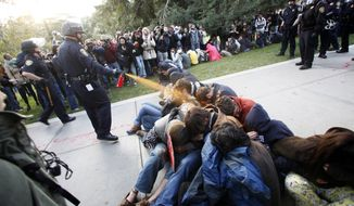 University of California, Davis Police Lt. John Pike uses pepper spray to move Occupy UC Davis protesters while blocking their exit from the school's quad in Davis, Calif., on Nov. 18, 2011. Two campus police officers involved in the pepper-spraying incident were placed on administrative leave two days later. (Associated Press/The Enterprise)