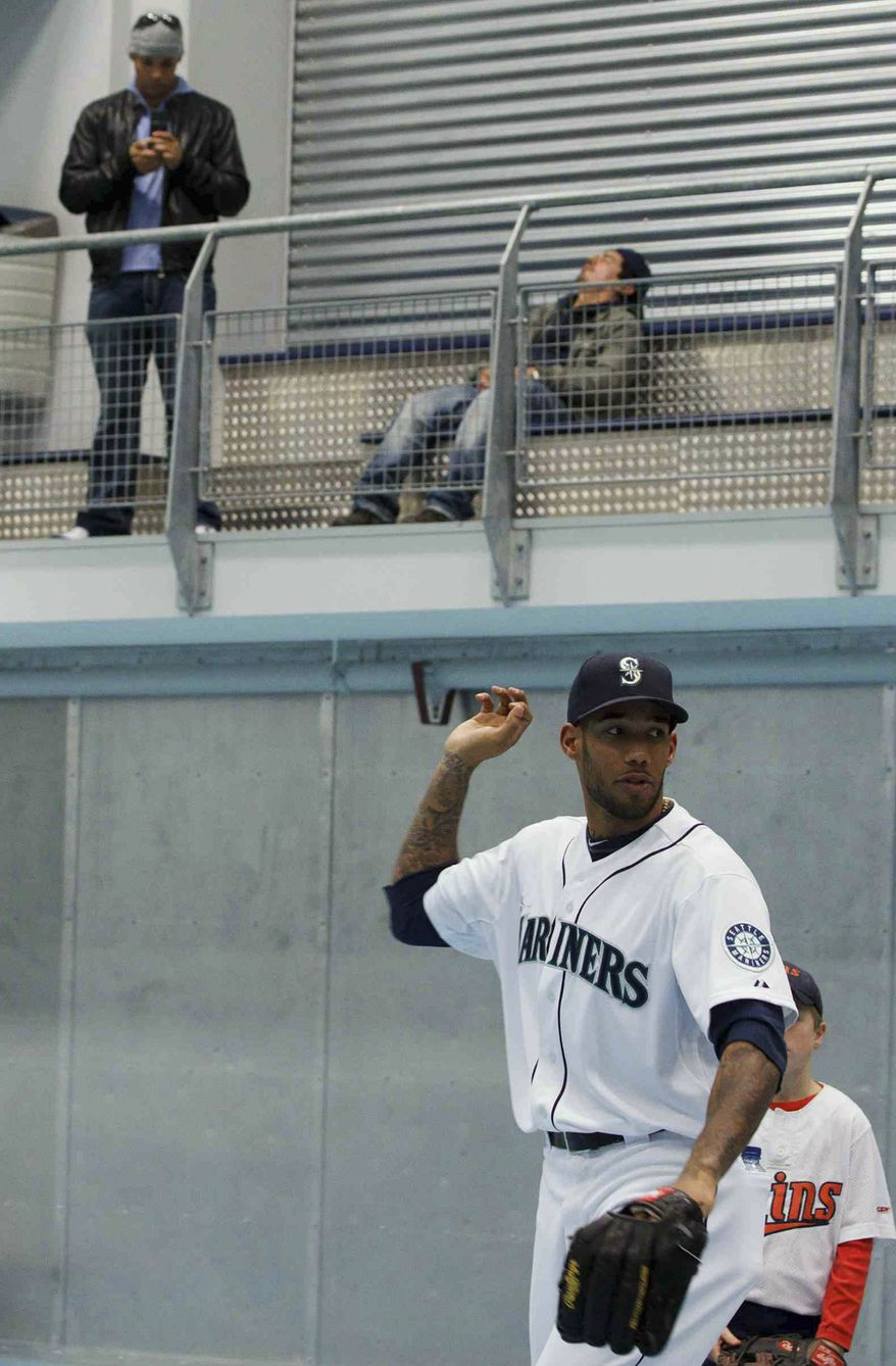 In this photo taken on Nov. 5, 2011, Seattle Mariners outfielder Greg Halman (foreground) is seen during a Big League Tour baseball game in Utrecht, Netherlands. His brother Jason Halman is seen at left in the background. Greg Halman was stabbed to death early Nov. 21, 2011 in Rotterdam, Netherlands, and his brother was arrested as a suspect, Dutch police said. (Associated Press)