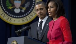 First lady Michelle Obama (right) speaks Nov, 21, 2011, at the White House before President Obama (left) signs legislation that will provide tax credits to help put veterans back to work. (Associated Press)