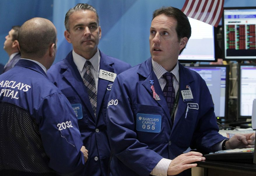 From left: Specialists James Denaro, Christopher Culhane and Glenn Carell work on the floor of the New York Stock Exchange on Nov. 21, 2011. (Associated Press)
