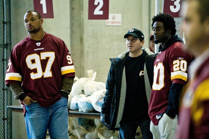 Owner Daniel Snyder (center) waits with linebacker Lorenzo Alexander (97) and safety Oshiomogho Atogwe to give out turkeys at the Redskins' annual Harvest Fest Tuesday at FedEx Field.