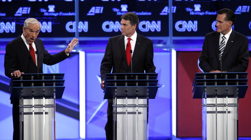 Republican presidential candidate Rep. Ron Paul of Texas speaks as Texas Gov. Rick Perry and former Massachusetts Gov. Mitt Romney listen at a Republican presidential debate in Washington on Nov. 22, 2011. (Associated Press)