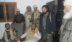 This image provided by the Libyan Youth Movement that was taken Saturday, Nov. 19, 2011, purports to show Seif al-Islam Gadhafi surrounded by revolutionary fighters following his capture near the Niger border with Libya. (AP Photo/Libyan Youth Movement)