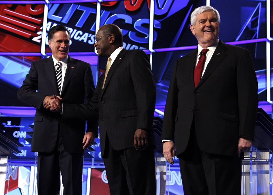 Republican presidential candidates from left, former Massachusetts Gov. Mitt Romney shakes hands with businessman Herman Cain, as former House Speaker Newt Gingrich stands on stage before a Republican presidential debate in Washington, Tuesday, Nov. 22, 2011. (AP Photo/Evan Vucci)