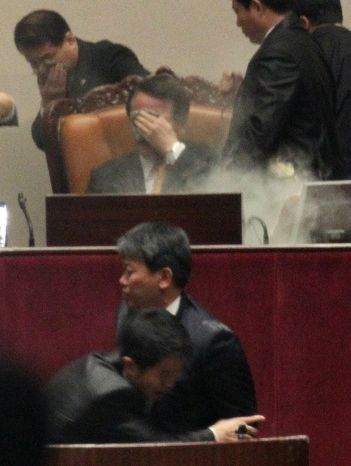 Rep. Kim Seon-dong of the opposition Democratic Labor Party (center bottom) is blocked Nov. 22, 2011, by a security officer as National Assembly Vice Speaker Chung Eui-hwa (center seated) covers his face after Kim exploded tear gas to try to block the passage of a bill on ratification of a South Korea-U.S. free trade agreement at the National Assembly in