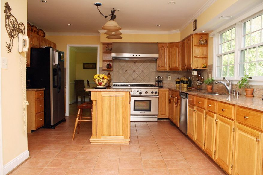 The kitchen features granite counters and a six-burner stove. It has ceramic tile floors and a center island with an overhang that can be used as a breakfast bar. The kitchen is adjacent to the family room