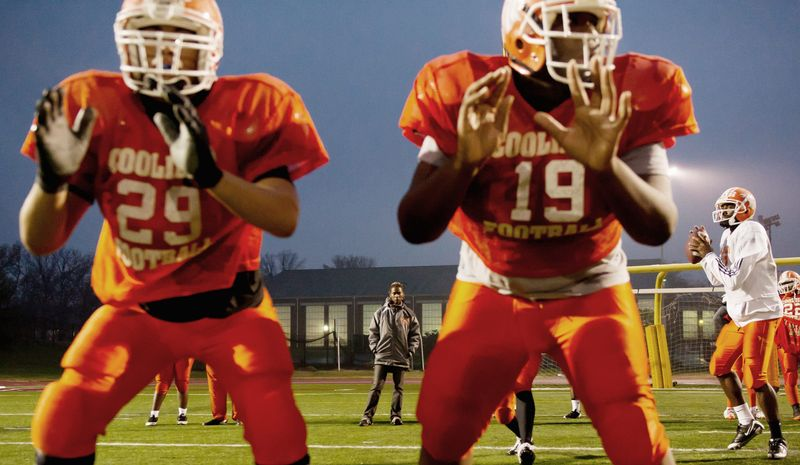 Coolidge High School varsity football coach Natalie Randolph (background) watches her players during a drill in preparation for the Turkey Bowl against Dunbar High School. She's in her second year of coaching and some of the novelty of a woman heading a boys football team has worn off. (Andrew Harnik/The Washington Times)