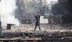 A protester gestures to Egyptian riot police during clashes near Tahrir Square in Cairo on Nov. 23, 2011. (Associated Press)