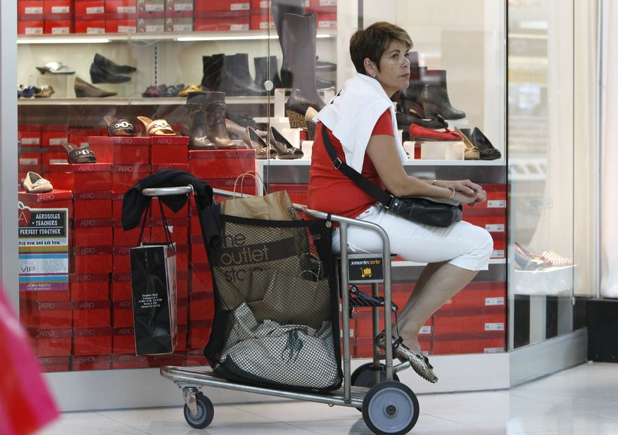 A tourist from Switzerland, who asked not to be identified, rests on her shopping cart while shopping Nov. 9, 2011, at Dolphin Mall in Miami. (Associated Press)