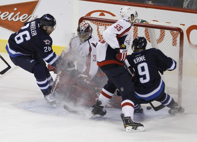 ** FILE ** Winnipeg Jets' Blake Wheeler (26) scores his first goal of the season on Washington Capitals' Michal Neuvirth (30) during second-period NHL hockey game action at MTS Centre in Winnipeg, Manitoba, Thursday, Nov. 17, 2011. (AP Photo/The Canadian Press, Trevor H
