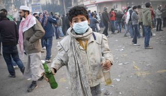 An Egyptian boy holds two Molotov cocktails during clashes with Egyptian riot police, unseen, in Cairo, Egypt, Wednesday, Nov. 23, 2011. (AP Photo/Mohammed Abu Zaid)