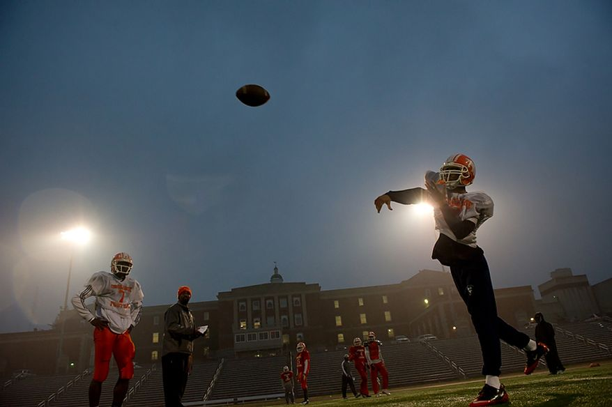 Coolidge High School's starting quarterback Femi Bamiro, left, and backup QB Darius Taylor, right, warm up before practice, Washington, DC, Monday, November 21, 2011. Coach Natalie Randolph gets her team ready for the Turkey Bowl. (Andrew Harnik/The Washington Times)