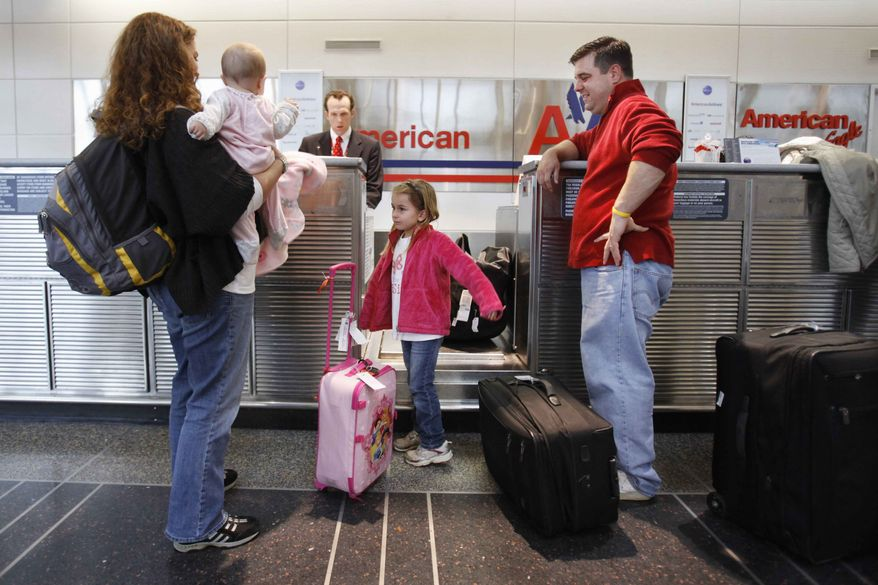 Lori Tempesta, of Falls Church, Va., left, holds her baby Ashlyn Tempesta, next to daughter Elena Tempesta, 3, and husband Anthony Tempesta, as they check in for a flight to Dallas for Thanksgiving, Wednesday, Nov. 23, 2011, at Washington's at Ronald Reagan National Airport. (AP Photo/Jacquelyn Martin)