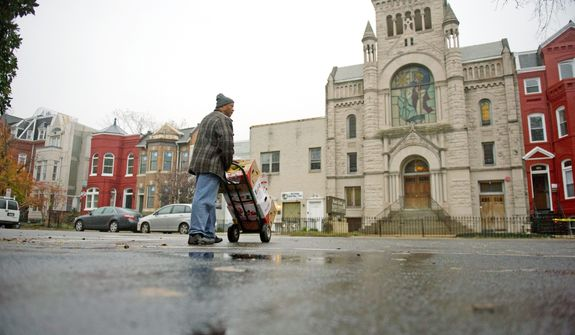 Central Union Mission staffer and former client Michelangelo Payne runs boxes of fresh fruit over to the Mount Gilead Baptist Church on 13th Street Northwest. (Rod Lamkey Jr./The Washington Times)