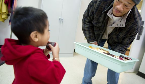 Michelangelo Payne offers cookies to Carlos Manuel Lopez, 3, as he makes his rounds cleaning up and organizing things at Mount Gilead Baptist Church. The mission's current programs serve homeless men; underprivileged women, children and seniors; veterans and the growing needs of the city's Hispanic community. (Rod Lamkey Jr./The Washington Times)