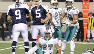 Dallas Cowboys quarterback Tony Romo and kicker Dan Bailey celebrate Bailey's game-winning field goal as Miami Dolphins cornerback Jimmy Wilson, Will Allen  and Nolan Carroll look on Thursday, Nov. 24, 2011, in Arlington, Texas. The Cowboys won 20-19. (AP Photo/Matt Strasen)