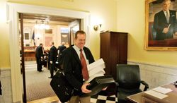 Del. Rob Bell, Albemarle Republican, carries papers and boxes out of the House of Delegates chambers after the House adjourned for the 2009 session in Richmond, Va.  (AP Photo/Steve Helber)