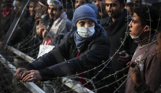 A woman protester attempts to dismantle a barbed wire barricade, newly erected by the Egyptian army, near Tahrir square in Cairo, Egypt, Thursday, Nov. 24, 2011. (AP Photo/Tara Todras-Whitehill)