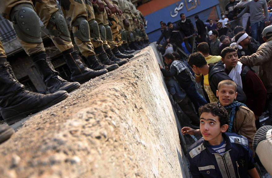 A boy looks at Egyptian Army soldiers standing guard atop a concrete block barricade on the street between Tahrir Square and the interior ministry in Cairo, Egypt, Thursday, Nov. 24, 2011. Police and protesters demanding that Egypt's ruling military council step down are observing a truce after five days of deadly street battles in which dozens have died. (AP Photo/Khalil Hamra)