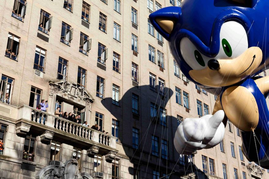 A balloon of video game icon Sonic the Hedgehog passes spectators on a balcony during Macy's Thanksgiving Day Parade.  (AP Photo/John Minchillo)