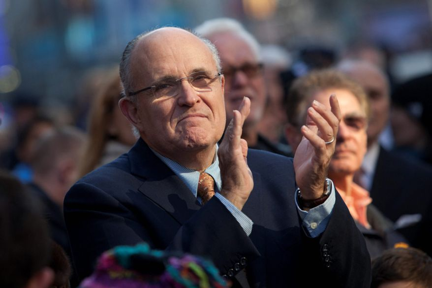 Former mayor of New York, Rudolph Giuliani watches  the Macy's Thanksgiving Day Parade in Times Square in New York. (AP Photo/Andrew Burton)